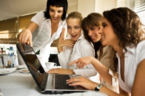 """Women attending an online event on their laptop"""